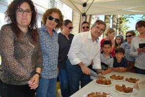 González, acomapañado de otros concejales, corta en porciones una de las cocas